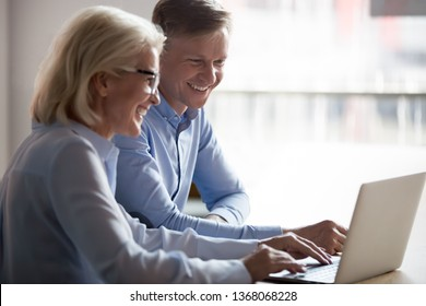 Happy manager and client having friendly conversation at meeting with laptop, smiling broker consulting customer showing computer funny presentation laughing talking watching online at work in office