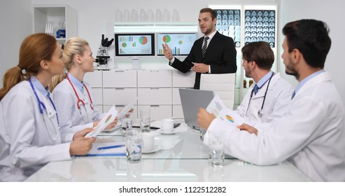 Happy Manager Man Positive Talking with Medical Doctors Team About Pie Chart Data in Hospital Cabinet or Healthcare Center Room
