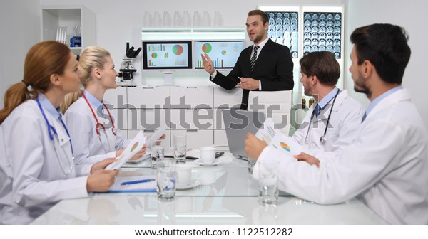 Happy Manager Man Positive Talking with Group of Medical Doctors Team About Hospital Management in Administrator Cabinet or Healthcare Center Administration Meeting Room