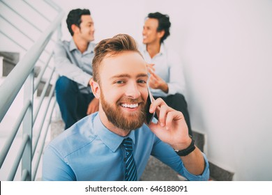Happy manager using phone and sitting on stairs