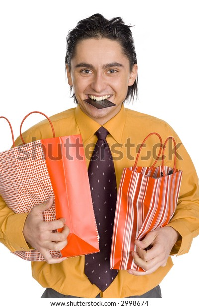 Happy man's carrying two paper bags. He's holding credit card by his teeth. Isolated on white in studio.