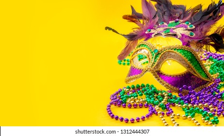 Happy Mardi Gras and Fat Tuesday carnival concept with close up on a face mask full of color, feathers and texture and golden, green and purple beads isolated on yellow background with copy space