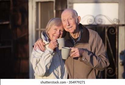Happy married couple with cups standing outdoors