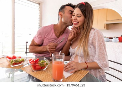Happy married couple having breakfast fruits and vegetables in the dining room of their house.