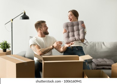 Happy married couple having fun while packing in modern living room on moving day, woman holding cushion cheerful man helping to unpack cardboard boxes on couch, settle move into new home relocation