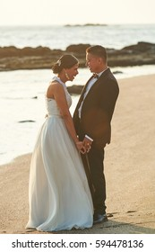 Happy married couple laughing in beach sunset time. Hispanic couple on wedding day