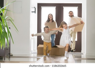 Happy married couple and little children arrive at new modern house. Husband and wife with cardboard boxes look at running inside excited daughter and son. Buy realestate, mortgage and moving concept