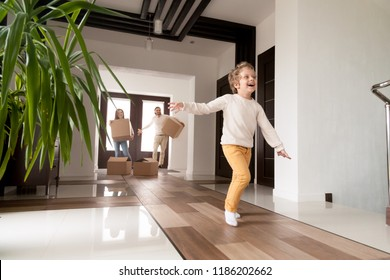 Happy married couple with little preschool son arriving in new house. Millennial first time buyers with cardboard boxes looking at running excited child. Buying real estate, mortgage, moving concept