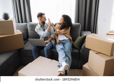 Happy married couple relocate to new apartment. Overjoyed young family approving interior house design, making good shopping online. Handsome man give high five to beautiful woman, teamwork concept