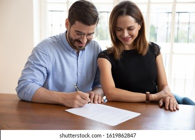 Happy married couple satisfied clients signing contract, making legal deal, smiling husband putting signature on documents, family purchasing real estate, new house, taking loan or mortgage