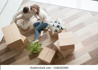 Happy married couple sitting on floor in living room, surrounded by unopened stuff in cardboard boxes. Wife and husband looking at each other with love, top above view. New home or real estate concept