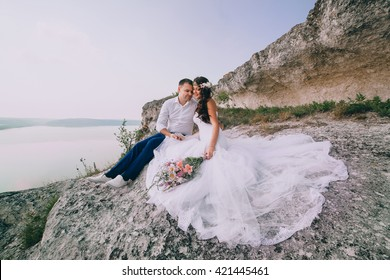 a happy married couple sitting on the rock near the lake