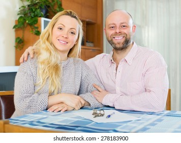 Happy married couple sitting at table with keys and documents