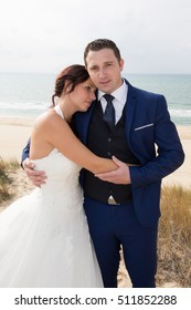 Happy married couple standing on the beach