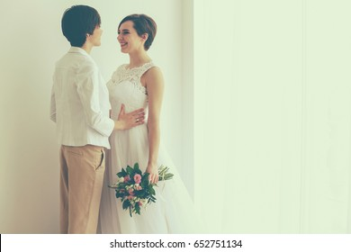 Happy married lesbian couple on light background