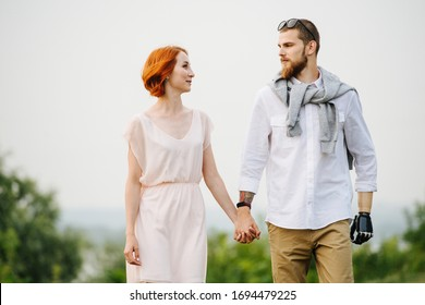 Happy married middle age couple walking slowly through a park next to a river. They are holding hands, looking at each other. Man has a prosthetic bionic arm.