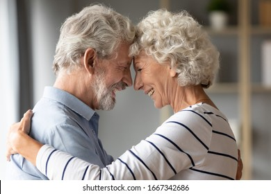 Happy mature 50s couple embrace touch foreheads look in the eyes show love and care at home, smiling elderly 60s husband and wife hug cuddle share close tender romantic moment together