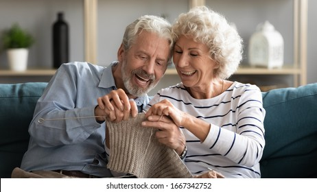 Happy mature 50s wife have fun teach knitting smiling 60s husband, overjoyed elderly retired couple spouses sit on couch in living room relax involved in hobby activities, spend weekend together