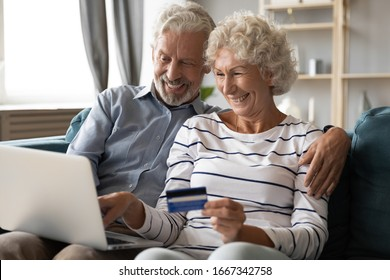 Happy mature 60s husband and wife sit on couch in living room buying things on internet on laptop, smiling excited elderly 50s couple customers shopping online at home with credit card use computer