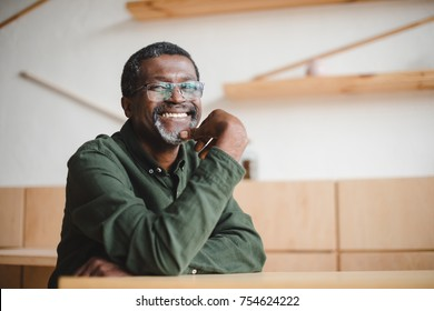 happy mature african american man sitting in cafe and looking at camera