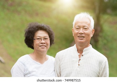 Happy mature Asian seniors couple at outdoor park.