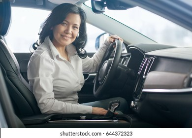 Happy mature Asian woman smiling to the camera joyfully sitting in a car at the dealership showroom copyspace owning buying choosing vehicle transport automobile comfort luxury lifestyle driving