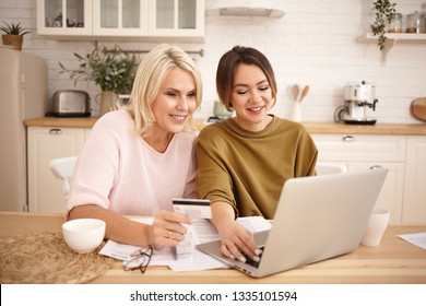 Happy mature blonde female holding credit card sitting at kitchen table with her cute young daughter, shopping online, buying new clothes, booking accomodation or airplane tickets, planning vacations