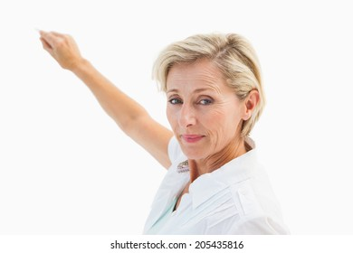 Happy mature blonde writing and smiling on white background
