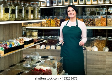 Happy mature brunette woman wearing apron and selling nuts and dried fruits in organic shop