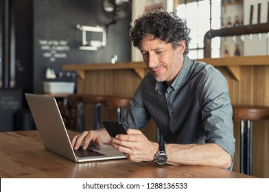Happy mature business man sitting at cafeteria with laptop and smartphone. Businessman texting on smart phone while sitting in a pub restaurant. Senior man working and checking email on computer.