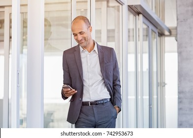 Happy mature businessman in formal using smartphone in modern office. Successful senior business man smiling on reading message on cellphone. Man using mobile phone in office.