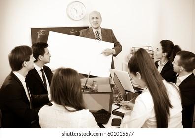 Happy mature businessman presents new development plan at poster