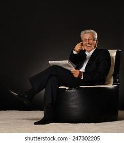 Happy mature businessman reading newspaper sitting on dark background