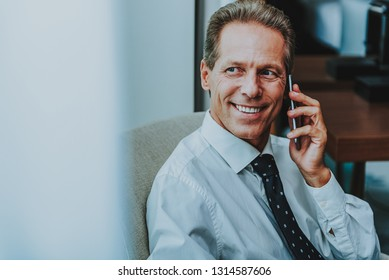 Happy mature businessman in shirt and tie sitting next to the window and smiling while talking on the phone and looking into the distance
