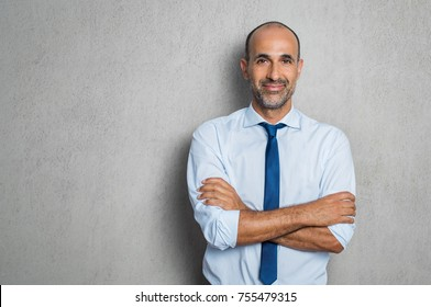 Happy mature businessman in shirt and tie looking at camera. Portrait of smiling and satisfied hispanic business man with arms crossed isolated over grey background with copy space. Successful senior