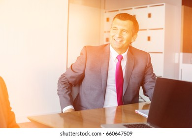 Happy mature businessman sitting at desk in office