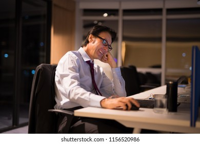 Happy Mature Businessman Sitting And Working In Office At Night