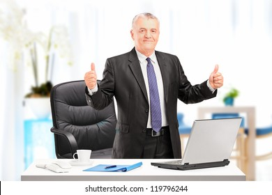 Happy mature businessman standing in his office and giving thumbs up