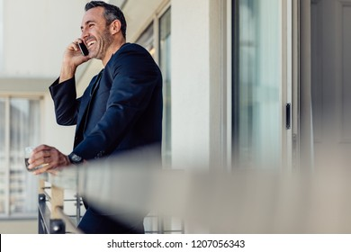 Happy mature businessman standing in hotel room balcony and making a phone  call. Smiling man 41b320952dc7
