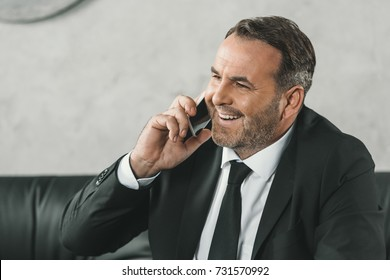 happy mature businessman talking by phone