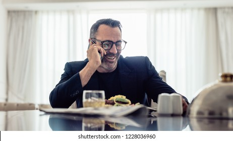 Happy mature businessman talking on mobile phone while sitting on dinning table in hotel room. Businessman having lunch and talking on phone in hotel room.
