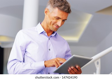 Happy mature businessman using electronic tablet