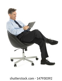 Happy mature businessman using tablet computer while sitting on office chair against white background
