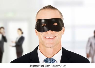 Happy mature businessman wearing eye mask