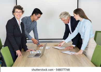 Happy mature businesswoman in boardroom with team