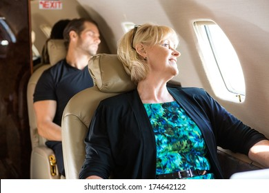 Happy mature businesswoman with man sleeping behind on private jet