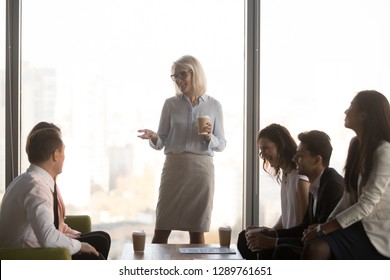 Happy mature ceo coach mentor leader talking to diverse team employees chatting at business meeting, friendly office workers group and middle aged female boss have fun conversation at coffee break