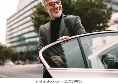 Happy mature commuter getting out of a taxi. Businessman getting off a cab.