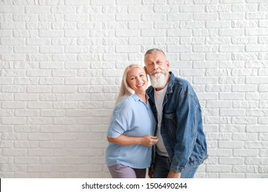 Happy mature couple against white brick wall