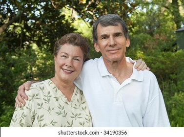 Happy mature couple, arms around each other outdoors.